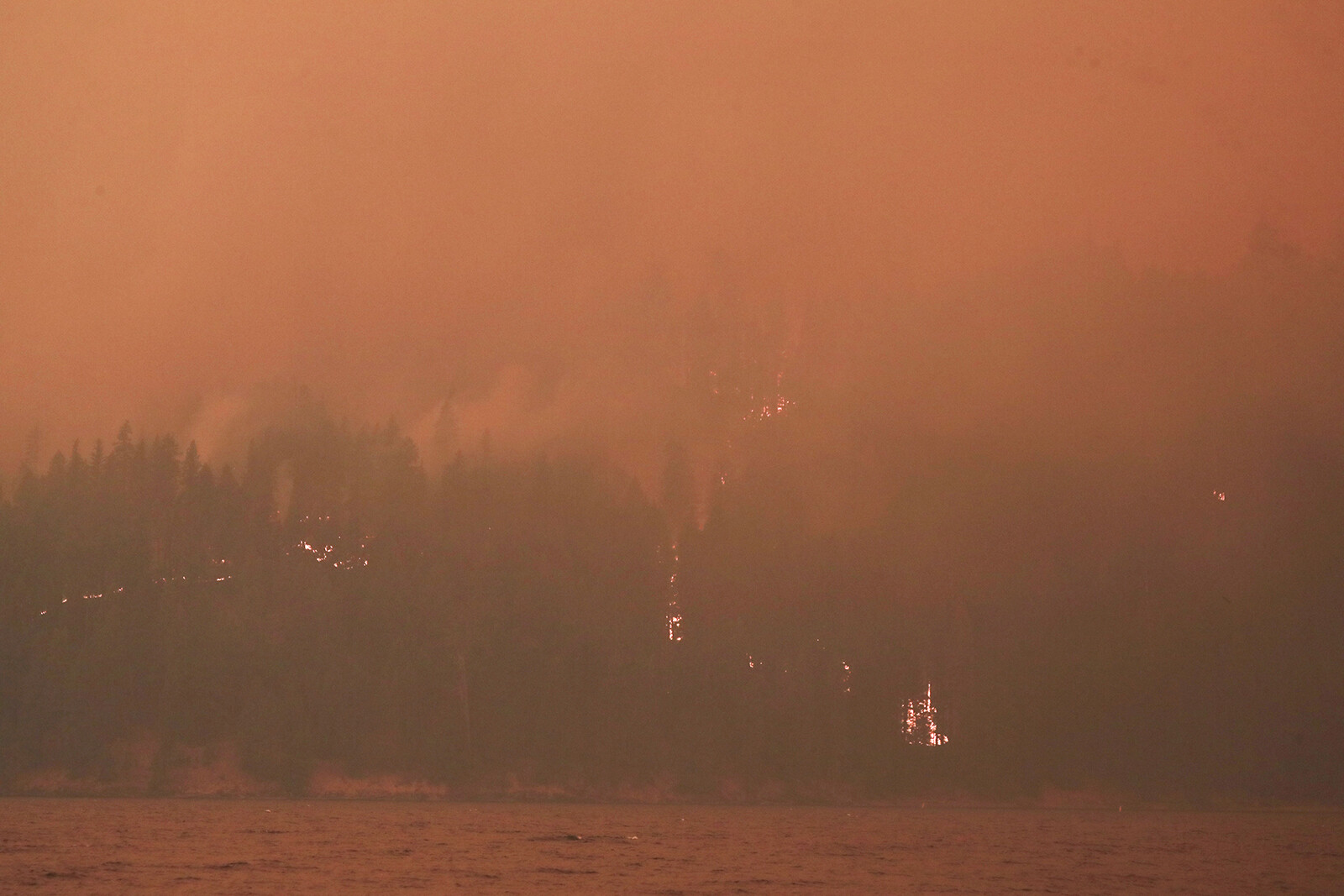 <i>John G. Mabanglo/EPA-EFE/Shutterstock</i><br/>Heavy smoke and flames on the west side of Butte Valley Reservoir from the Dixie fire in Plumas County