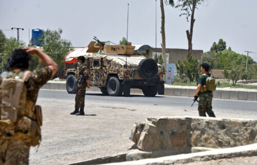 Afghan security personnel stand guard along a road during an ongoing fight between Afghan forces and Taliban fighters in Kandahar on July 9.