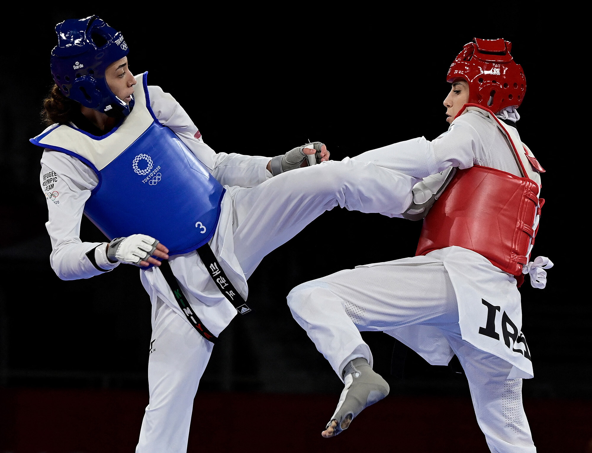 <i>Javier Soriano/AFP/Getty Images</i><br/>Refugee Olympic Team's Kimia Alizadeh (Blue) and Iran's Nahid Kiyani Chandeh (Red) compete in the taekwondo women's -57kg elimination round bout during the Tokyo 2020 Olympic Games at the Makuhari Messe Hall in Tokyo on July 25.