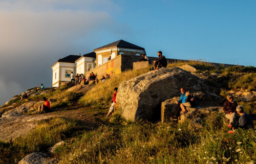 Pilgrims and tourists are seen waiting for the sunset at the Cape Finisterre. Cape Finisterre is the destination of those pilgrims who