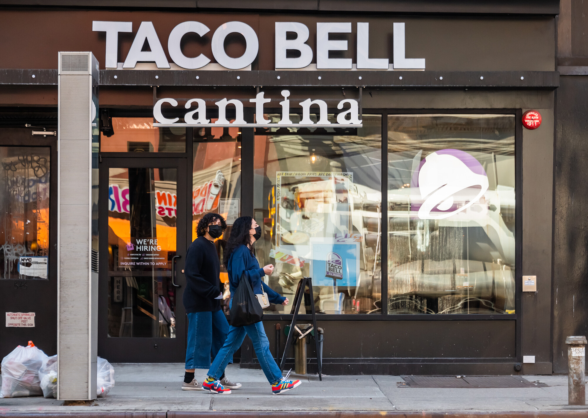 <i>Noam Galai/Getty Images</i><br/>Two people wearing masks walk by a Taco Bell Cantina on March 21 in New York City. The chain apologized on its website July 20