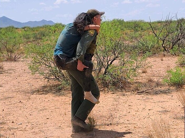 A Border Patrol agent carries a dehydrated migrant woman on his back for medical care.