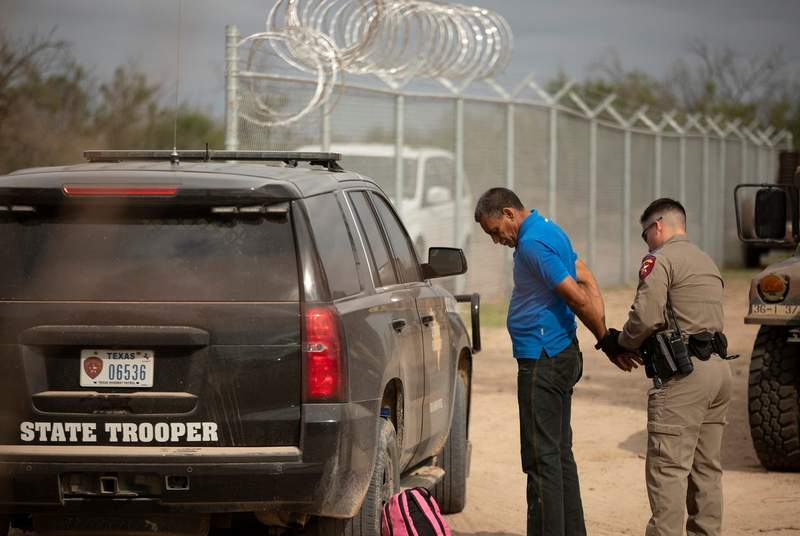 A Texas Department of Public Safety trooper arrests a Venezuelan migrant, on private riverside property in Del Rio, just beyond a newly installed fence paid for by the state.