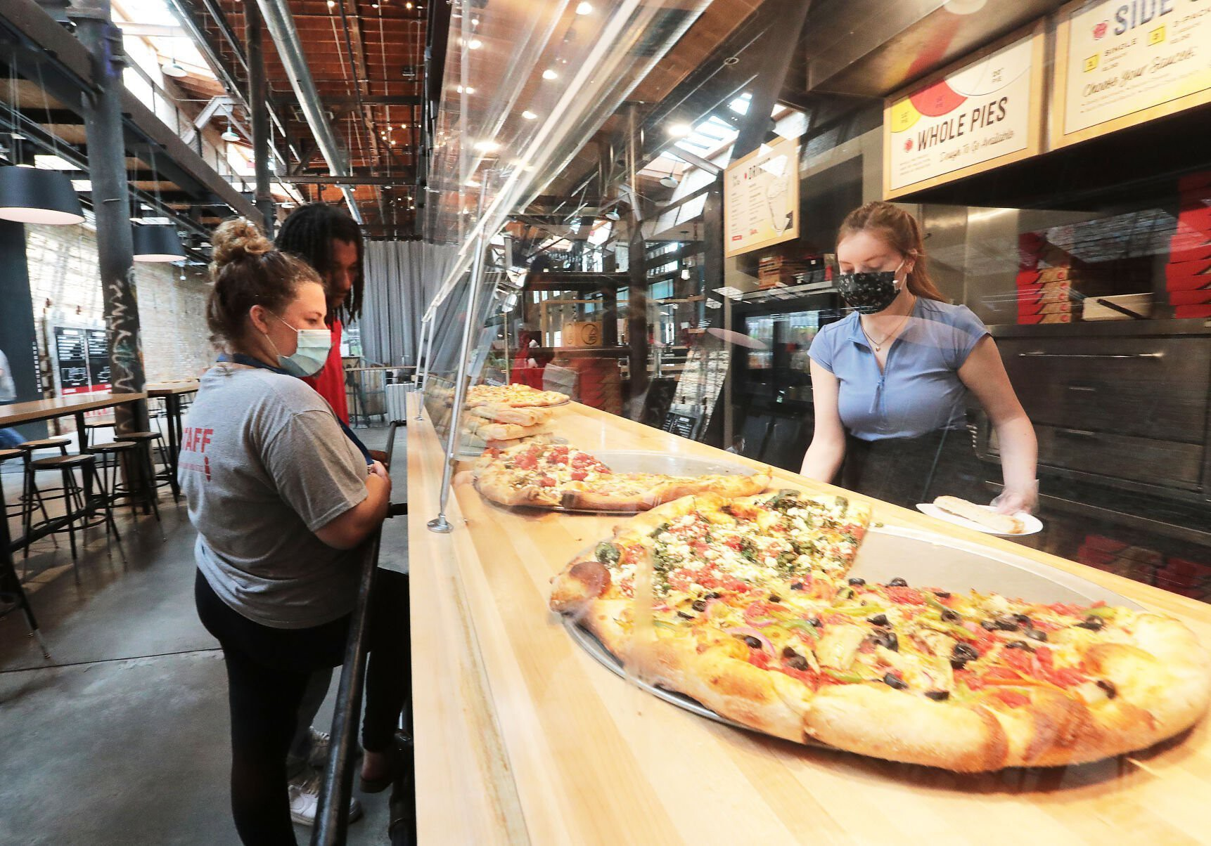 <i>John Hart/Wisconsin State Journal</i><br/>Ian's Pizza worker Stella Klein serves customers Olivia Rebholz and Randy Bland at the restaurant's Garver Feed Mill location. Only three of the chain's seven restaurants were approved for federal COVID-19 grant assistance.