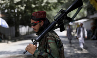A Taliban fighter stands guard at a checkpoint in the Wazir Akbar Khan neighborhood in the city of Kabul