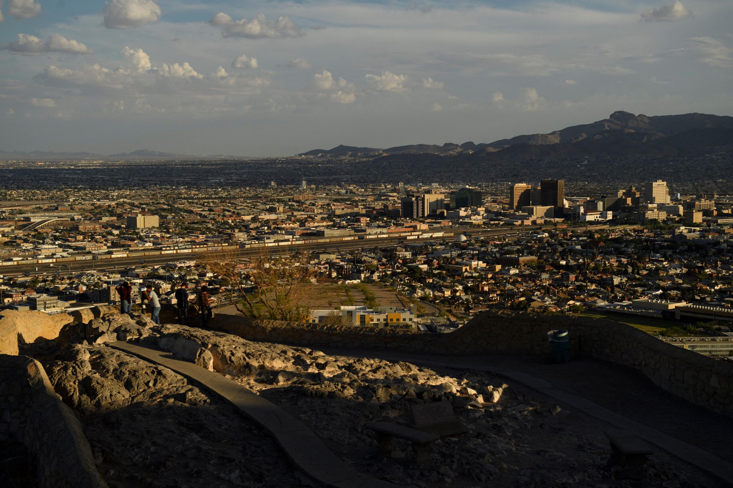 People look towards the downtown El Paso and the US-Mexico border separating El Paso and Ciudad Juarez from Murchison Rogers Park along Scenic Drive at sunset.