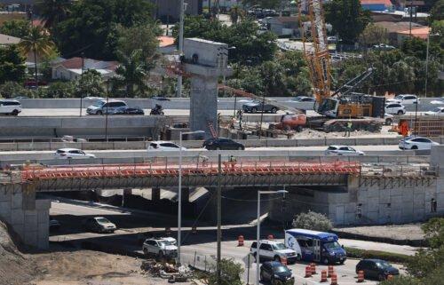 "Construction workers build the ""Signature Bridge"