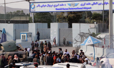 Taliban fighters stand guard as Afghans gather outside the Hamid Karzai International Airport to flee the country