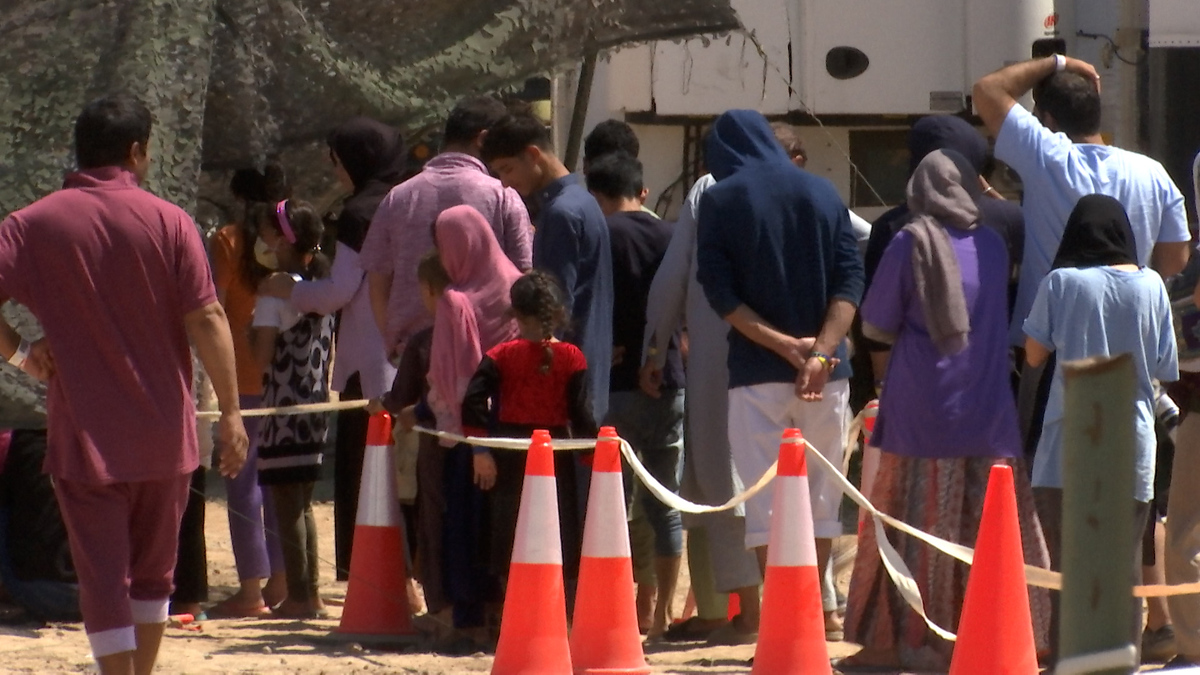 Afghan refugees wait in a food line at their Fort Bliss housing complex.