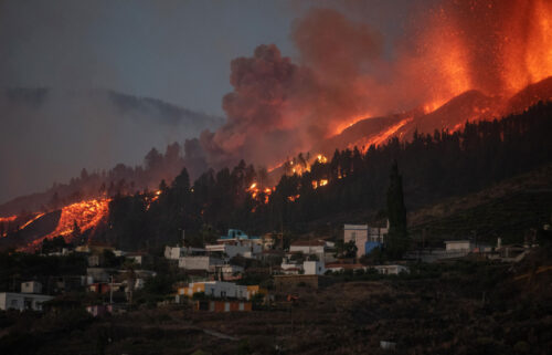 A river of lava flowing from the volcano approaches houses on Spain's La Palma island on Sunday.