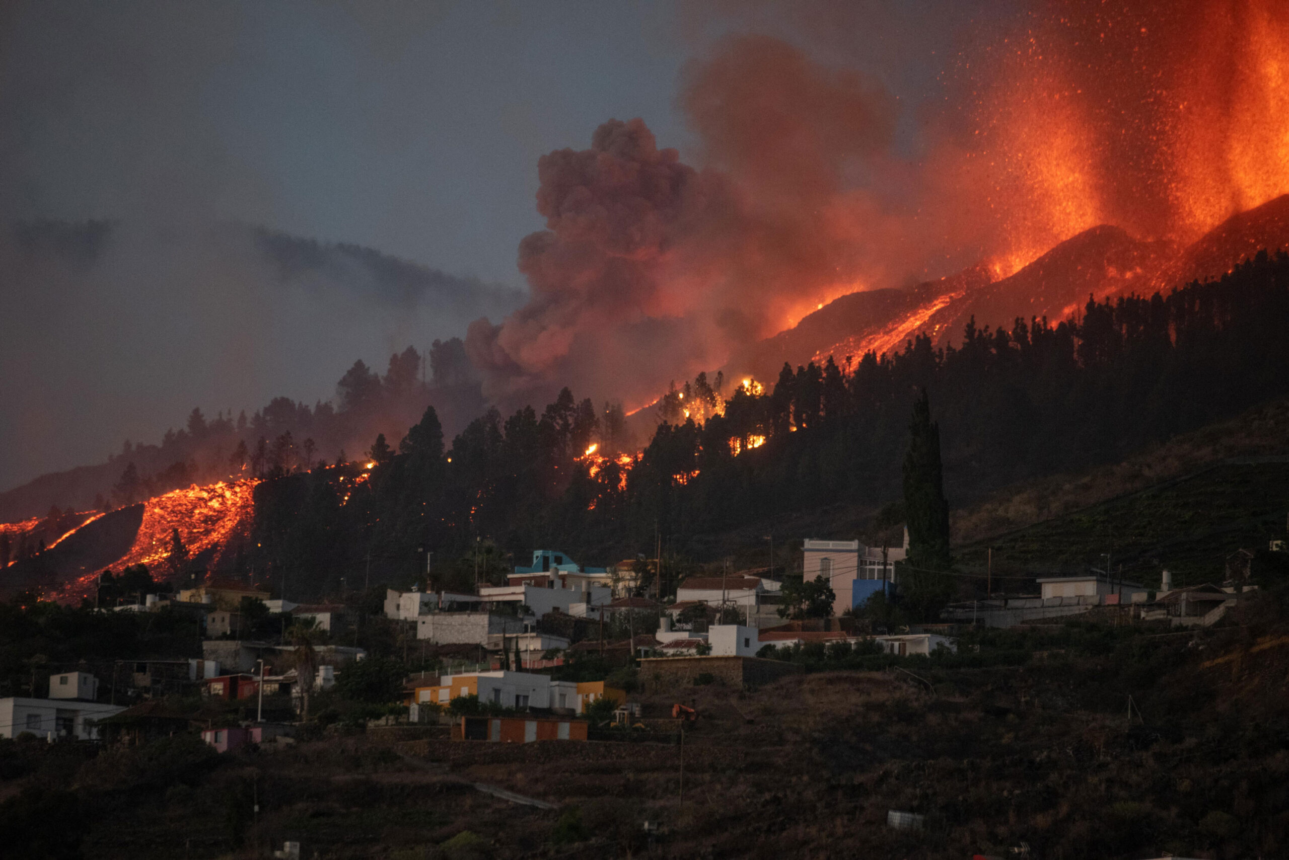 <i>Desiree Martin/AFP/Getty Images</i><br/>A river of lava flowing from the volcano approaches houses on Spain's La Palma island on Sunday.