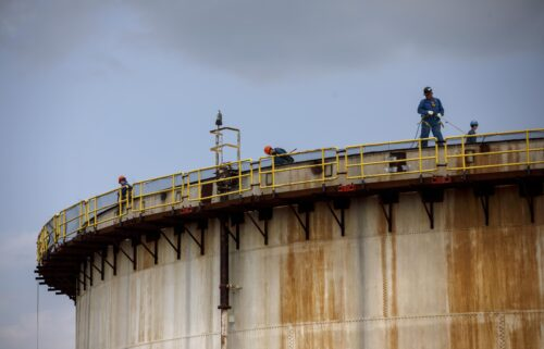 The world must limit global warming to 1.5 degrees Celsius above pre-industrial levels to limit climate crisis. Workers here stand atop a storage tank at an Imperial Oil Ltd. refinery in Sarnia