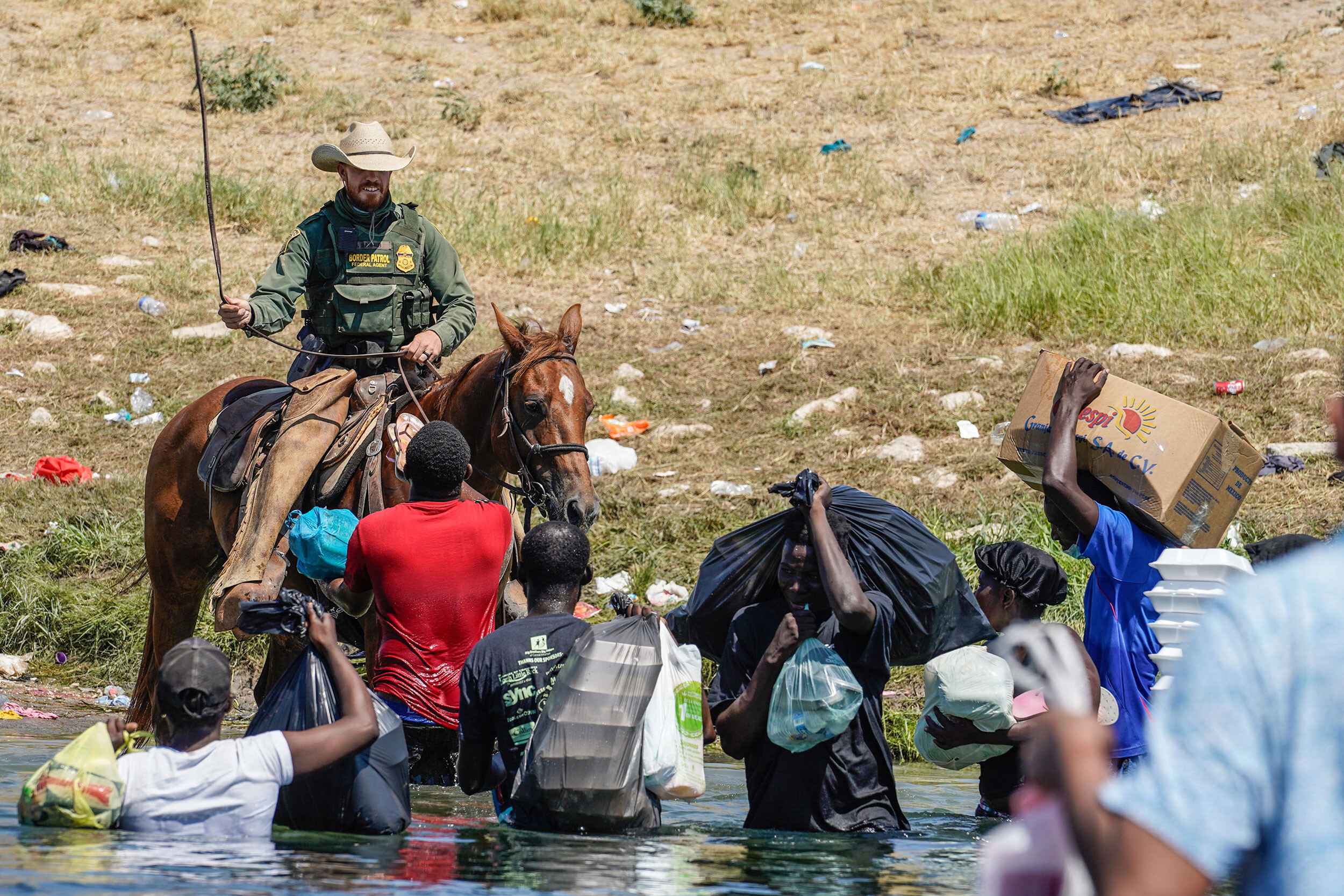 <i>Paul Ratje/AFP/Getty Images</i><br/>A United States Border Patrol agent on horseback uses the reins as he tries to stop Haitian migrants from entering an encampment. The DHS has since temporarily suspended the use of horse patrol.
