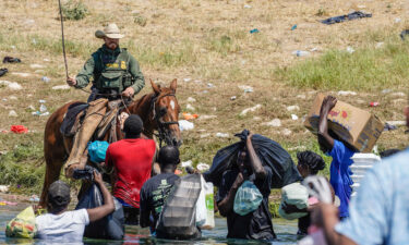 A United States Border Patrol agent on horseback uses the reins as he tries to stop Haitian migrants from entering an encampment on the banks of the Rio Grande near the Acuna Del Rio International Bridge in Del Rio