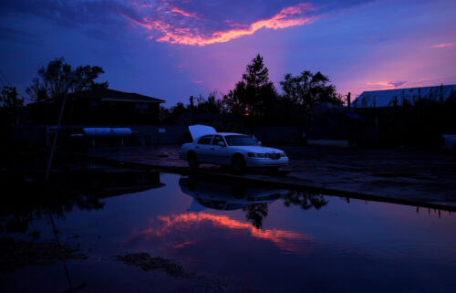 Car prices are about to soar again. Blame Hurricane Ida. A damaged car sits beside floodwaters in the aftermath of Hurricane Ida in Jean Lafitte