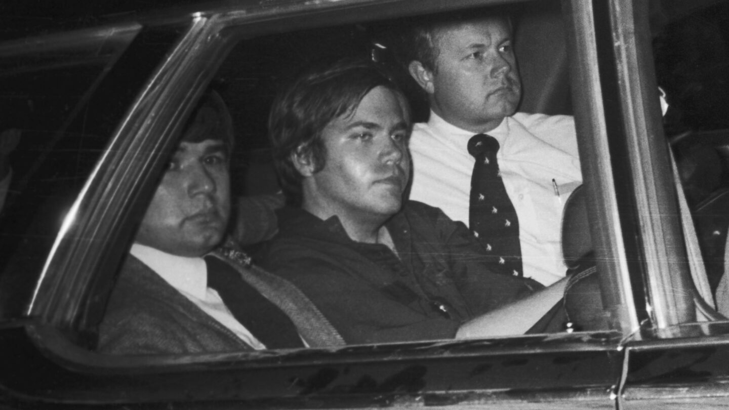 In this file photo from April 1981, John Hinckley, Jr. is driven away from U.S. District Court. Hinckley was seated in the center seat .