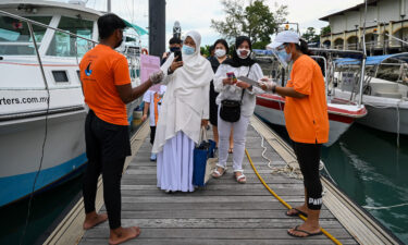 Passengers scan an app to monitor their health status before boarding a yacht in Langkawi