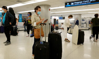 Travelers gather their luggage as they arrive at Miami International Airport on September 20.