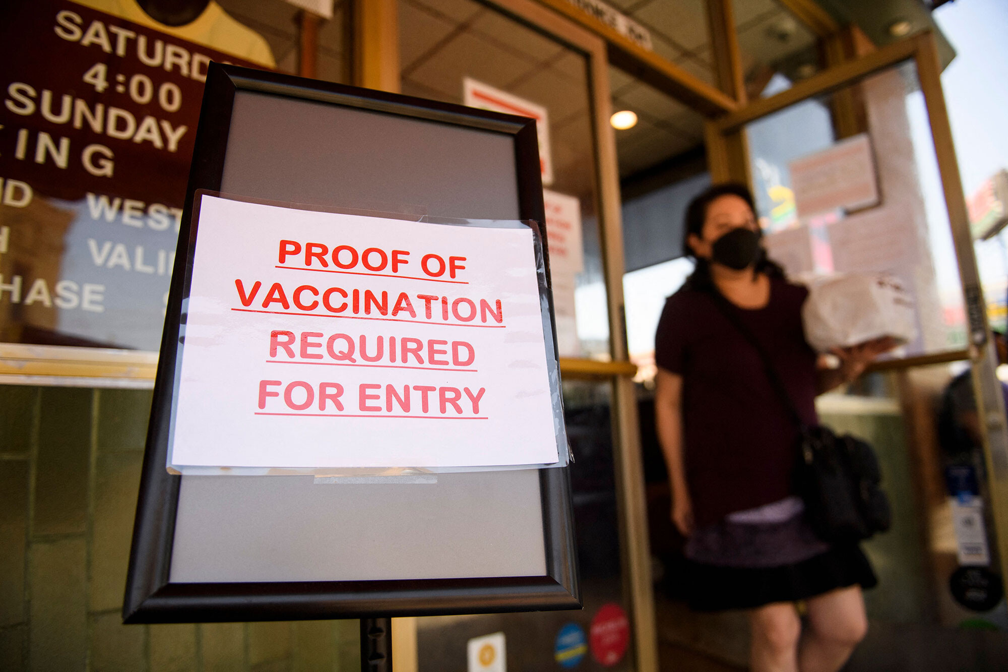 <i>Patrick T. Fallon/AFP/Getty Images</i><br/>A sign stating proof of a Covid-19 vaccination is required is displayed outside of Langer's Deli in Los Angeles on August 7.