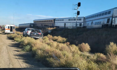 In this photo provided by Kimberly Fossen an ambulance is parked at the scene of an Amtrak train derailment on Saturday