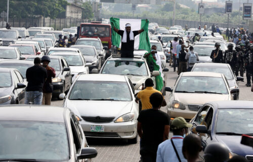 A demonstrator raises a Nigerian flag from a car during a motorcade to mark the one-year anniversary of the #EndSARS protest at the Lekki toll gate in Lagos