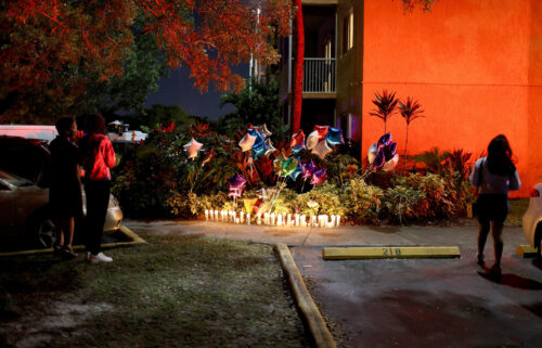 """People stand near the memorial on the spot where 18-year-old Dwight """"DJ"""" Grant's body was found near his home on October 26 in Miramar"""