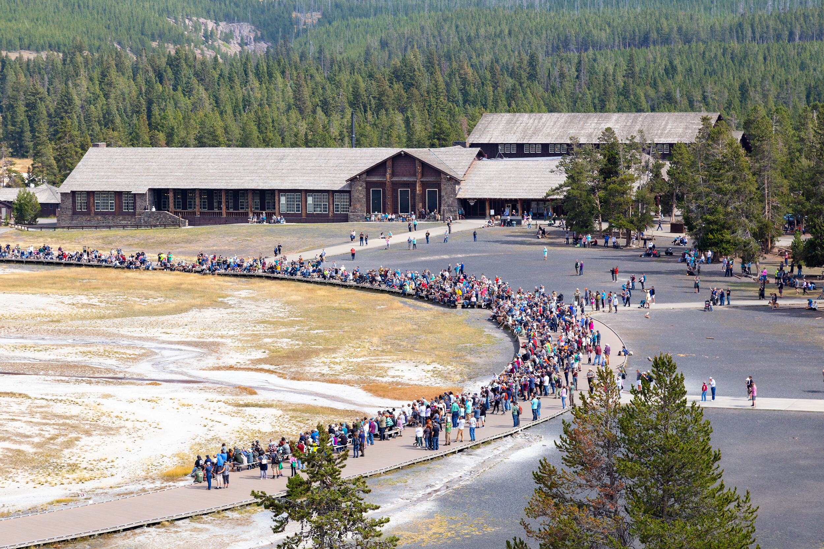 <i>Jacob W. Frank/NPS</i><br/>Crowds gather for an afternoon Old Faithful geyser eruption in September 2021.