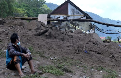 A resident sits near houses at the scene of a landslide triggered by a 4.8 magnitude earthquake at Trunyan village in Bangli