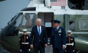 US President Joe Biden is greeted by Col. Matthew Jones (R)