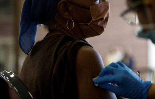 A nurse sanitizes a patient's arm before administering a Covid-19 vaccine booster during a Pfizer-BioNTech vaccination clinic in Southfield