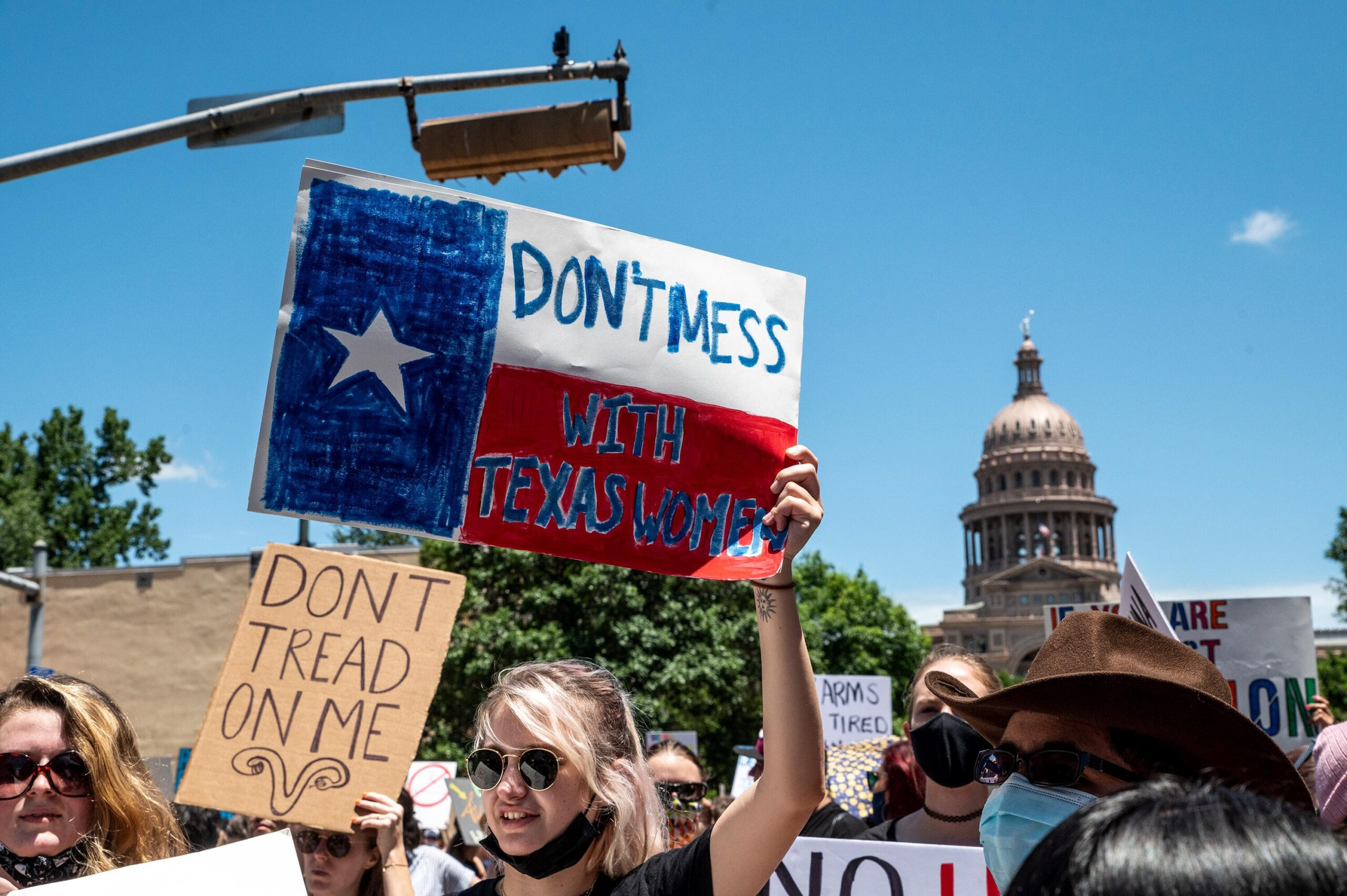 <i>Sergio Flores/Getty Images</i><br/>A federal judge Friday questioned Texas abortion ban's controversial enforcement mechanism. Abortion protesters hold up signs outside the Texas state capitol on May 29